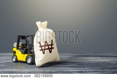 Forklift Transports A South Korean Won Money Bag. Crisis Recovery Measures. Attraction Of Investment