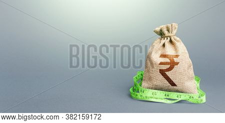 Indian Rupee Money Bag And Measuring Tape Meter. Analysis Of Economic Situation. Formation And Optim
