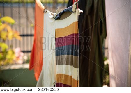 Clothes On The Clothesline. Garments Exposed To The Sun. Backyard Of Residential House With Washed C