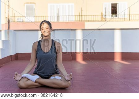 Happy And Smiling Young Woman Practicing Yoga, Meditation And Mindfulness On Her Terrace, Lotus Posi