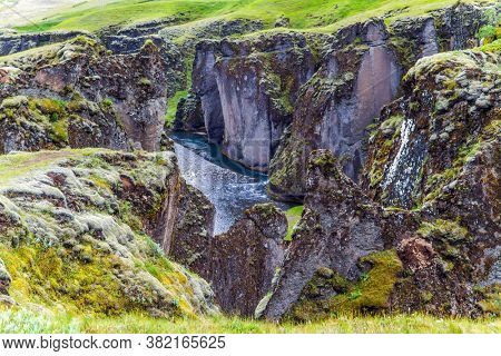 The Fyadrarglyufur Canyon, Iceland. Sheer cliffs covered with green moss. River with glacial water flows between bizarre cliffs. The concept of active, eco and photo tourism