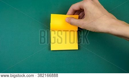 Woman's Hand Tears Off A Yellow Sheet With An Adhesive Edge For Notes On A Green Background, Copy Sp