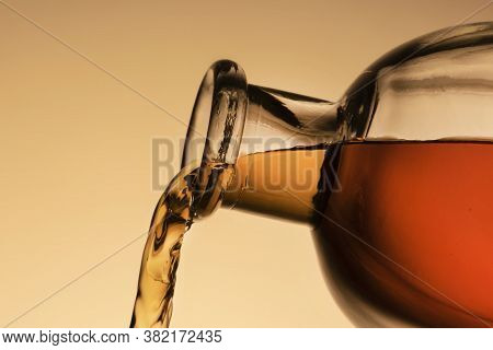A Bottle Of Whiskey, Bourbon, Or Liqueur. Pouring Liquid, A Stream From The Neck. Close - Up Orange