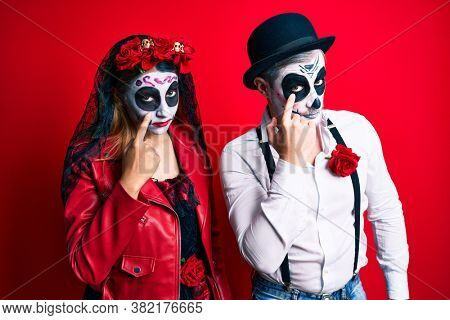 Couple wearing day of the dead costume over red pointing to the eye watching you gesture, suspicious expression