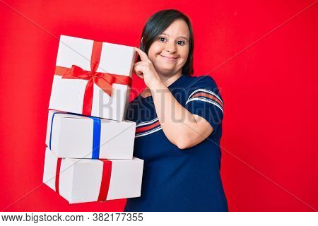 Brunette woman with down syndrome holding gifts smiling with a happy and cool smile on face. showing teeth.