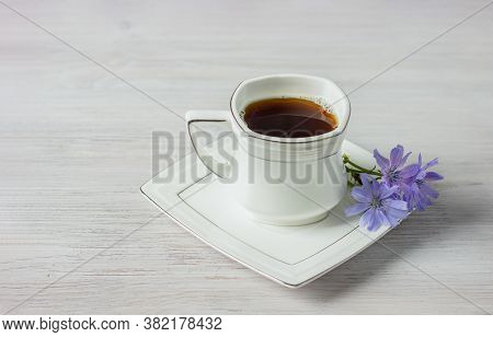 White Cup Of Instant Chicory Drink Or Coffee With Chicory Flowers On A White Table. Healthy Food Con