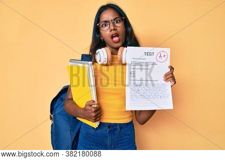 Young indian girl wearing backpack showing a passed exam in shock face, looking skeptical and sarcastic, surprised with open mouth