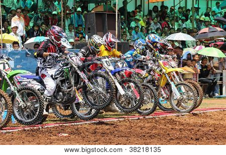 Motocross Riders Lined Up At The Start Gate