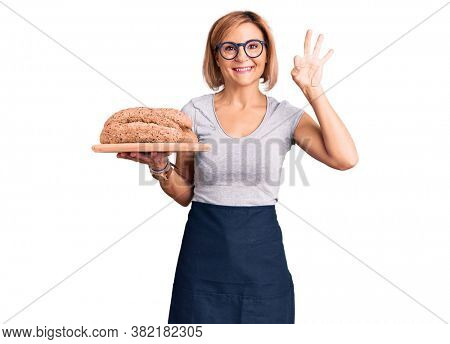 Young blonde woman holding wholemeal bread doing ok sign with fingers, smiling friendly gesturing excellent symbol
