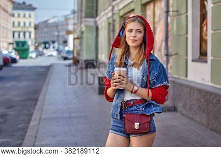 Beautiful Young Caucasian Cheerful Woman About 25 Years Old With Blond Hair And In Red Hoodie Is Wal