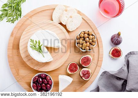 Traditional Spanish Cuisine Appetizers With White Brie Cheese, Figs, Olives And Rose Wine On White T