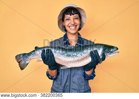 Beautiful brunettte fisher woman showing raw salmon smiling with a happy and cool smile on face. showing teeth.