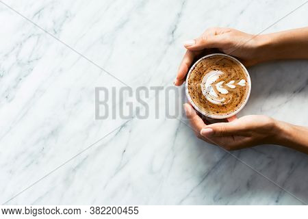 Pink Cup Of Fresh Cappuccino In Woman Hands On White Marble Table Background. Classic Latte Art And