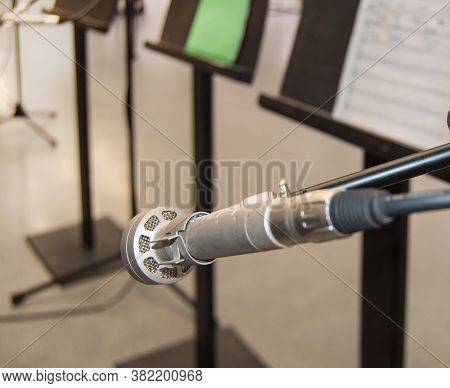 Microphone And Music Notes On A Music Stand On A Blurred Background, Dof, Side View