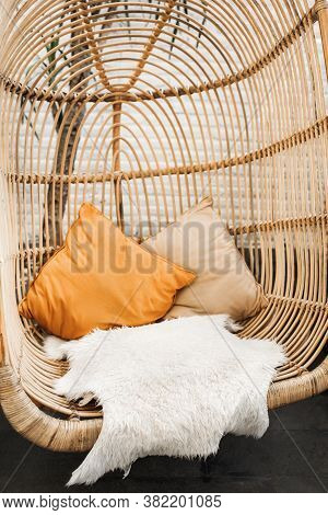 Wicker Rattan Hanging Chair In Loft Cafe. Eco Friendly Furniture Style And Concept. Orange Pillows A