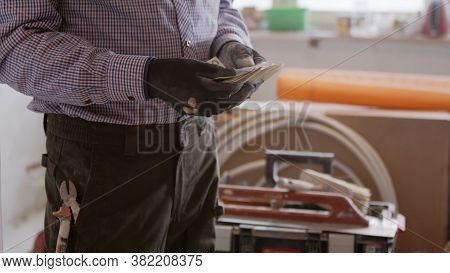Handy Man Counting The Money After Repair. High Quality Photo