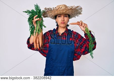 Beautiful brunettte woman wearing farmer clothes holding fresh carrots puffing cheeks with funny face. mouth inflated with air, catching air.