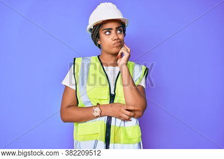 Young african american woman with braids wearing safety helmet and reflective jacket serious face thinking about question with hand on chin, thoughtful about confusing idea