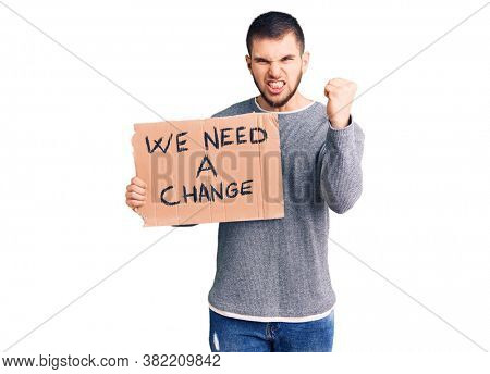 Young handsome man holding we need a change banner annoyed and frustrated shouting with anger, yelling crazy with anger and hand raised