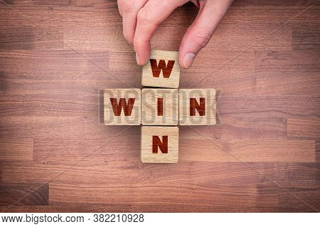 Win-win Cooperative Strategy Concept. Businessman Hand Complete Wooden Jigsaw Wit Text Win.
