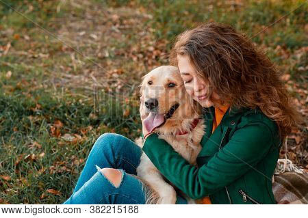 Happy Woman Rest With Her Dog Golden Retriever. Female Girl Enjoying Outdoor With Her Pet. Woman Is