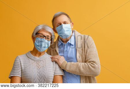 Senior couple wearing facemask during coronavirus and flu outbreak. Virus and illness protection, home quarantine. COVID-2019. Taking on or taking off masks.
