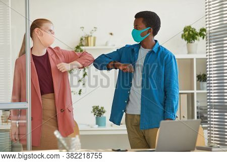 Portrait Of Young Woman Wearing Mask Bumping Elbows With African-american Colleague As Contactless G