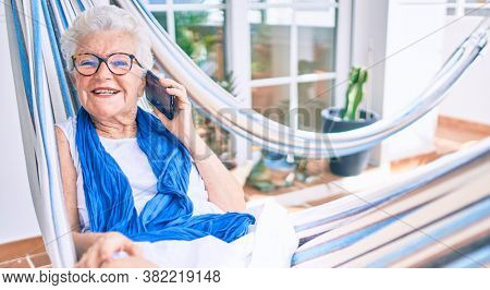 Elder senior woman with grey hair smiling happy relaxing on a hammock at home speaking on the phone