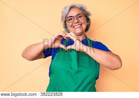 Senior hispanic woman wearing apron and glasses smiling in love showing heart symbol and shape with hands. romantic concept.