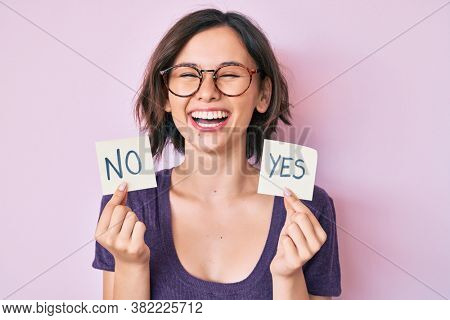 Young beautiful girl holding yes and no reminder smiling and laughing hard out loud because funny crazy joke.