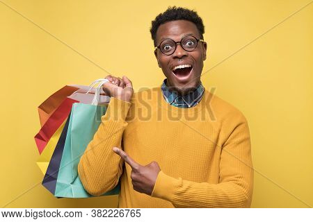 Handsome African Man With Shopping Bags Pointing On His Shopping Bags.