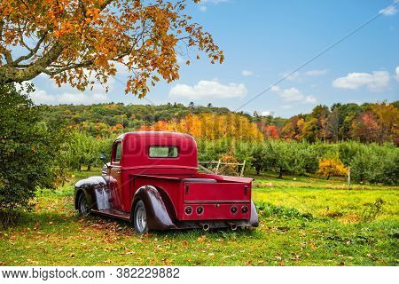 Bowdoin, Maine - October 12, 2018: Old Antique Red Farm Truck In Apple Orchard Against Autumn Landsc