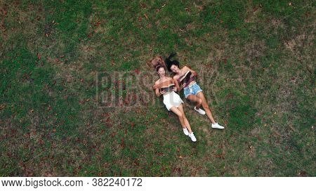 couple of friends lying on a meadow reading