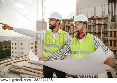 Serious Male Supervisor And Engineer Checking Blueprint And Discussing Plan Of Building While Inspec