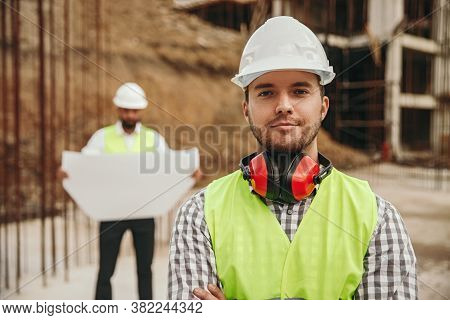 Positive Young Bearded Male Engineer In Hardhat And Waistcoat With Protective Headphones Looking At