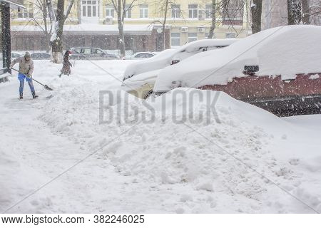 Car In Snow. Car Parked Near Home Parked Into Snow. Woman Cleaning Snow.