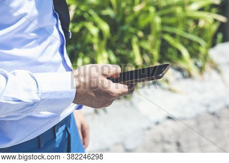 Young Man Holds The Phone In His Hand