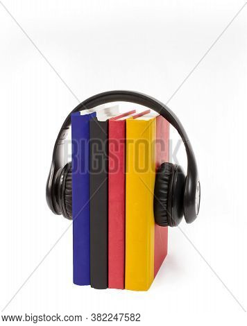 Vertical Shot Of Four Colorful Books Standing On End Wearing Black Headphones.  White Background.  C