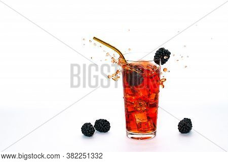 Glass With Black Berry Cocktail On A White Background. The Berry Falls Into The Glass And Sprinkles