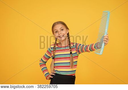 Comb Not Just For Blonde. Happy Child Hold Blue Comb Yellow Background. Little Girl Smile With Plast