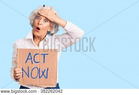 Senior grey-haired woman holding act now banner stressed and frustrated with hand on head, surprised and angry face