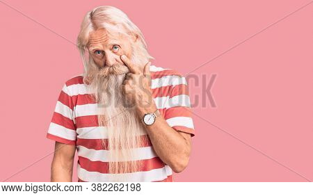 Old senior man with grey hair and long beard wearing striped tshirt pointing to the eye watching you gesture, suspicious expression