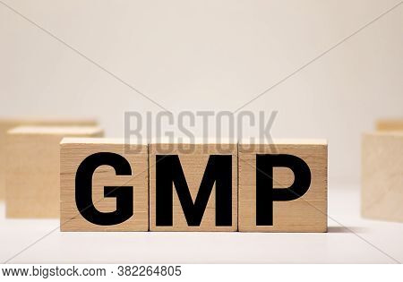 Good Manufacturing Practice. Gmp The Word On Wooden Cubes, Cubes Stand On A Reflective Surface, In T