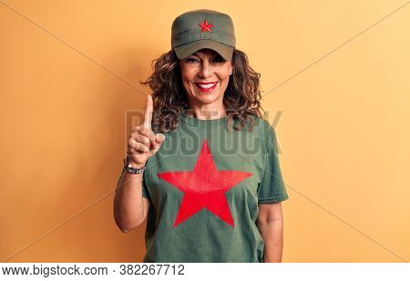 Middle age brunette woman wearing t-shirt and cap with red star symbol of communism smiling with an idea or question pointing finger up with happy face, number one