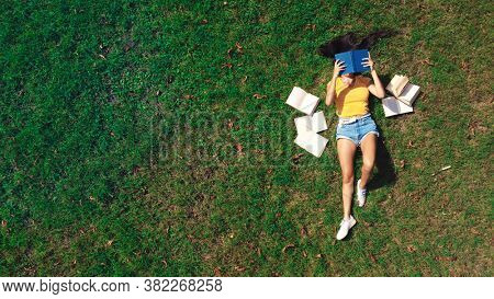 girl lying on a green lawn reads a book