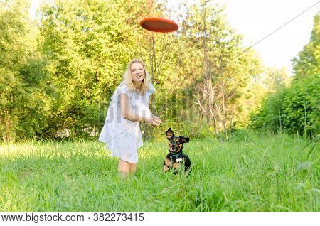 A Beautiful Blonde Young Woman Throws A Frisbee After Which A Dog Runs.