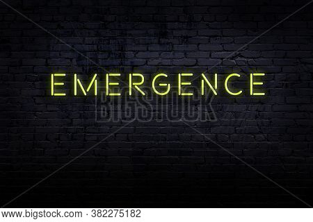 Neon Sign On Brick Wall At Night. Inscription Emergence