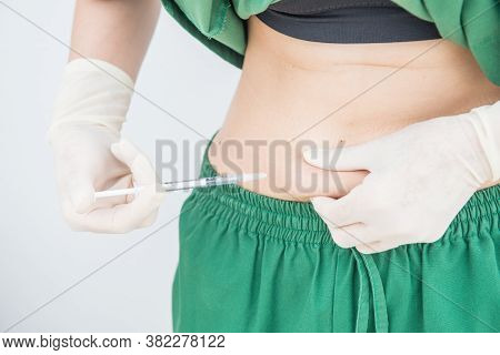 Shot Of Woman Hand With Syringe Inject Insulin To Her Belly. Diabetes Injection And Health Care Conc
