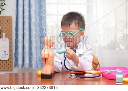 Cute Little Asian 4 Years Old School Boy In Doctor Uniform Playing Doctor At Home, Kid Wearing Steth
