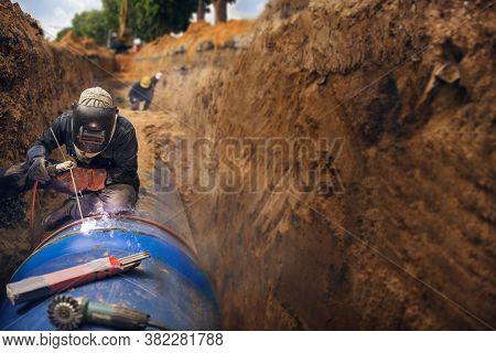 Welder Working Welding Pipeline Underground Installation In Construction Site Wearing Safety Mask Eq